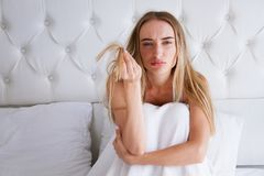 Health And Beauty. Portrait Of Beautiful Sad Young Woman With Long Hair In Hand. Unhappy girl lies on bed in bedroom royalty free stock photo