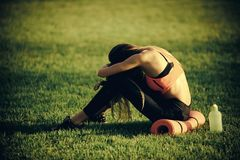 Health, bodycare, wellness. Tired woman in sportswear relax after workout, training. Sportswoman sit on green grass with gym equipment on summer. Backache royalty free stock photo