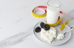Health breakfast.Concept of diet and lose weight.Kefir,spoon with cottage cheese on circle plate,prunes and yellow measure tape royalty free stock photos