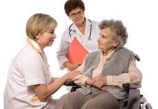 Health care. Workers and elderly woman in wheelchair Stock Photos