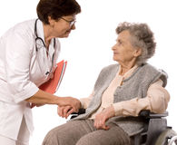 Health care. Worker and elderly woman in wheelchair Stock Photos