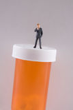 Health Care. Miniature business man standing on pill bottle Stock Photos