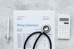 Health care billing statement with doctor`s stethoscope and pen on stone background top view Royalty Free Stock Photos