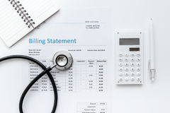 Health care billing statement with doctor`s stethoscope on white background top view mock-up. Health care billing statement with doctor`s stethoscope on white Stock Photo