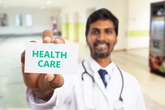 Health care card presented by medic. White health care card with green text presented by smiling indian medic close-up stock image