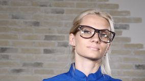 In health care clinic. Portrait of female doctor or intern in blue uniform putting on glasses smiling. 4k. In health care clinic. Portrait of female doctor or stock video
