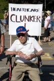 Health Care Clunker Wheelchair. Senior citizen sitting in a wheel chair with a Health Care Clunker sign Royalty Free Stock Photo