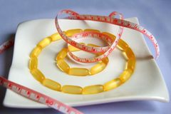 Health care concept. Diet pills and a tape measure isolated on white plate Stock Photo