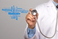 Health Care Concept. Doctor holding a stethoscope and medicare w. Ord on gray background stock image
