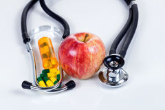 Health care concept with medicine plus red apple with stethoscop Royalty Free Stock Photography