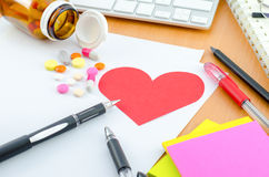 Health Care Concept - Red heart with supplement on computer desk Royalty Free Stock Photography