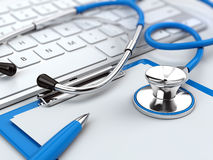 Health care concept - stethoscope on laptop keyboard with clipboard and pen Stock Images