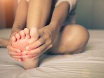 Health care concept. woman massaging her painful foot. Red hi-lighted on pain area royalty free stock photos