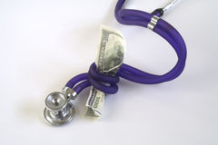 Health Care Cost. Stethoscope squeezing hundred dollar bill like a snake Royalty Free Stock Image