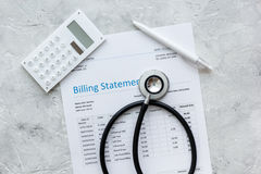 Health care costs with billing statement, stethoscope and calculator on stone table top view. Health care costs with billing statement, stethoscope and Royalty Free Stock Photography
