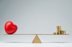 Health care costs. Red heart shape and money coins stack balancing on a seesaw Royalty Free Stock Image
