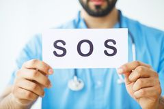 Health Care. Doctor Holding a Card With Symbol SOS, Medical Conc. Ept Royalty Free Stock Photography