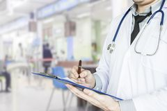 Health care, emergency room physician Writing a patient illness report. At hospital stock photo