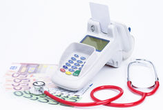 Health care expenses. Credit card machine with banknotes and stethoscope isolated on white stock photos