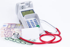 Health care expenses. Credit card machine with banknotes and stethoscope isolated on white stock photo