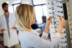 Health care, eyesight and vision concept - happy woman choosing glasses at optics store. Health care, eyesight and vision concept - happy beautiful women royalty free stock photography