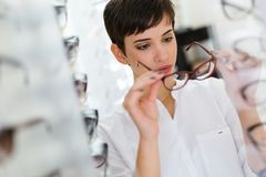 Health care, eyesight and vision concept - happy woman choosing glasses at optics store Royalty Free Stock Photo