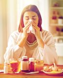 Sick woman with medicine blowing nose to wipe Stock Photography