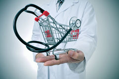 Health care industry. Doctor holding in his hand a shopping cart with a stethoscope inside, depicting the health care industry concept royalty free stock images