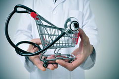 Health care industry. Doctor holding in his hand a shopping cart with a stethoscope inside, depicting the health care industry concept stock image