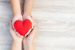 Adult and child hands holding handmade red heart on wooden background. royalty free stock photo