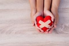 Health care, love, organ donation, family insurance and CSR concept. Adult and child hands holding handmade red heart on wooden background. First Aid Band stock image