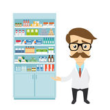 Health care. Male pharmacist in pharmacy opposite shelves with medicines Royalty Free Stock Photo