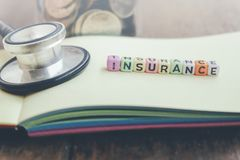 Health care management concept word block INSURANCE on yellow book over wooden background Stock Image