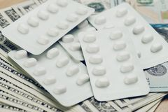 Health care and medical industry concept, white package of pills. On pile of US dollar banknotes, cost and expense that patient have to pay for their better Stock Photo