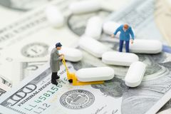 Health care, medical or pharmaceutical industry business concept. Miniature worker using forklift to manage or move white tablet pills on US dollar money Royalty Free Stock Image