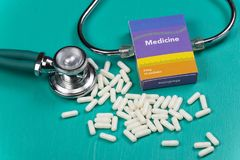Health care medical and sickness concept. Pills and medical equipment background with a drug box fake write & x22;Medicine. Stethoscope white capsule view top royalty free stock photography