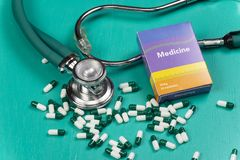 Health care medical and sickness concept. Pills and medical equipment background with a drug box fake write & x22;Medicine. Stethoscope white capsule view top stock images