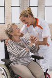 Health care nurse holding elderly lady's hand Stock Photos