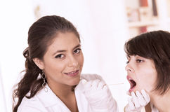 Health care professional checking patient's throat Stock Image