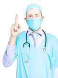 Health care professional pointing to copyspace. Health care professional in a gown and mask with a stethoscope around his neck pointing above his head with his Royalty Free Stock Photo