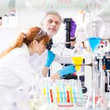 Health care professionals in lab. Attractive young female scientist and her senior male supervisor looking at the microscope slide in the life science research Stock Image
