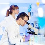 Health care professionals in lab. Young male researcher looking at the microscope slide in the life science laboratory. Female asistant scientist working in the Royalty Free Stock Photos