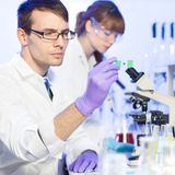 Health care professionals in lab. Young male researcher looking at the microscope slide in the life science laboratory. Female asistant scientist working in the Royalty Free Stock Photo