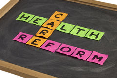 Health care reform crossword. Colorful sticky notes on a school blackboard with white chalk texture Stock Photos