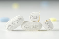 Health Care Reform debate laws Obamacare. The difficulties of universal health care reform Obamacare laws and mandate represented on pills in a stack with a Stock Photo