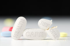Health Care Reform debate laws obamacare. Stack of pills with HEALTH CARE REFORM stamped in pills with the REFORM pill broken in half representing the Stock Photography