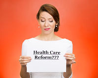 Health care reform?. Portrait skeptical female citizen professional doctor holding sign health care reform? isolated red background. Obamacare medicaid Royalty Free Stock Images