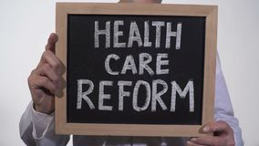 Health care reform text on blackboard in doctor hands, state government policy