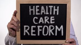 Health care reform text on blackboard in doctor hands, state government policy. Stock footage royalty free stock photography