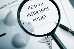 Health care search. Magnifying glass over health insurance policy and piggy bank Stock Photo